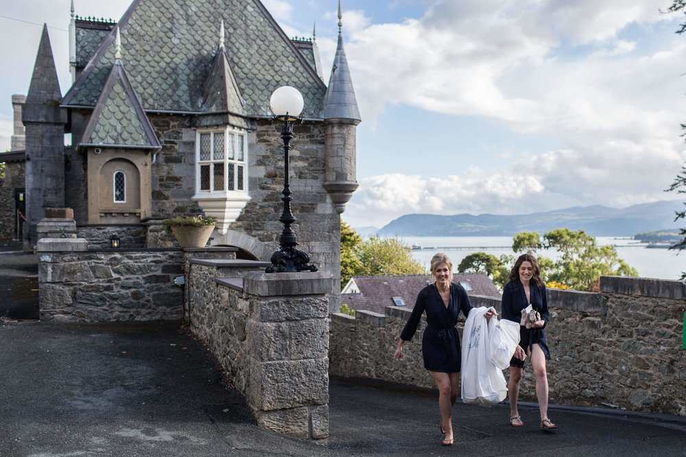bride carrying dress for preparation with menai strait backdrop
