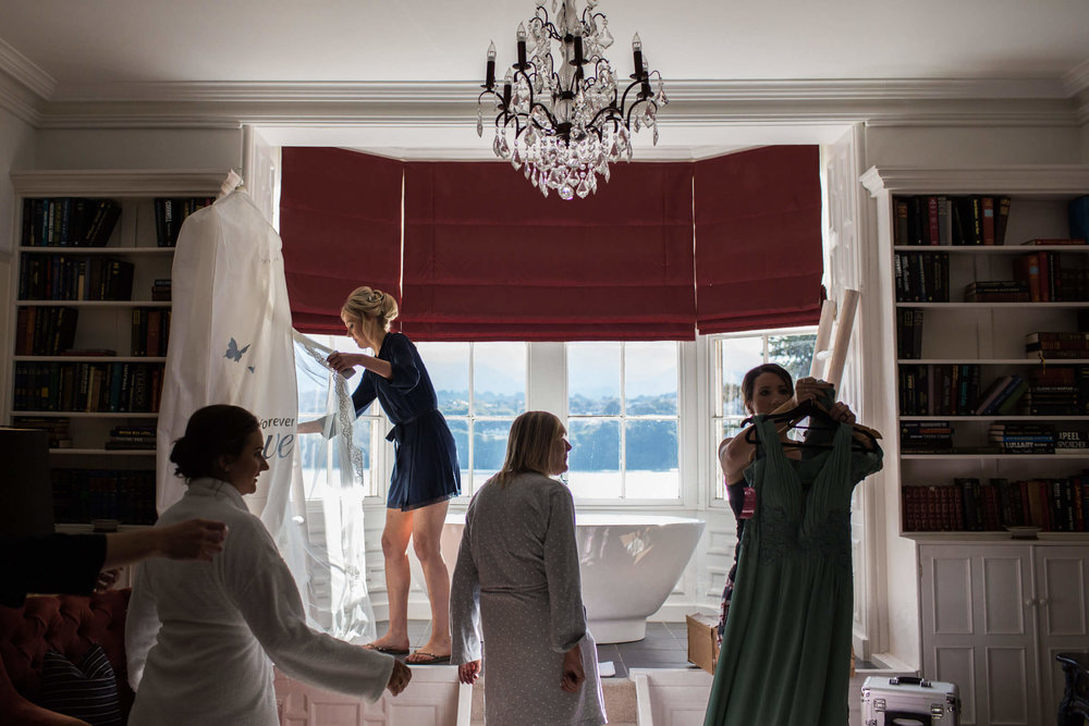 bride hanging up dress in bridal suite