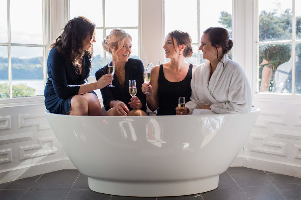 bride and bridesmaids in the bath together being chilled and relaxed
