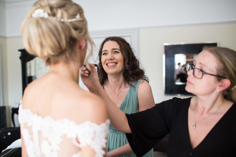 bridesmaid smiling at bride having make-up