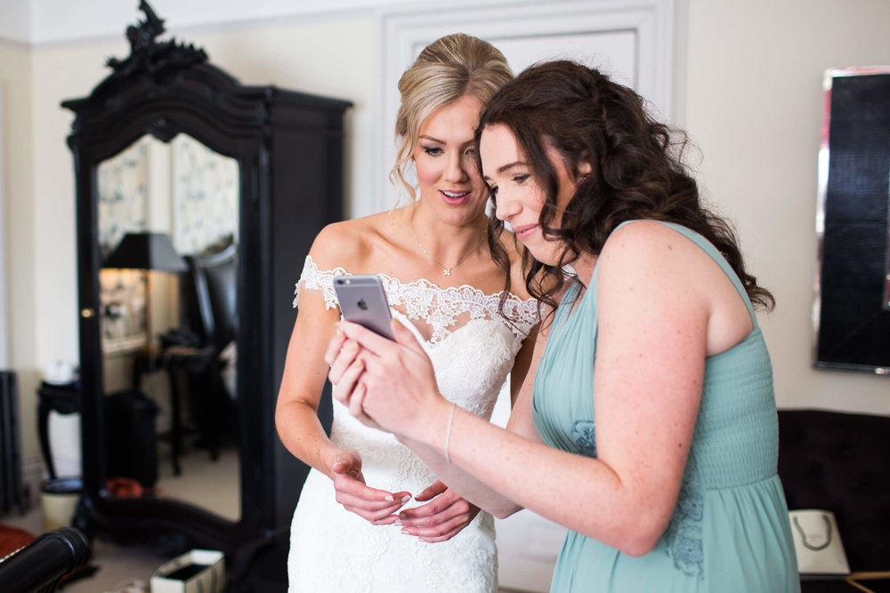 bridesmaid and bride looking at phone