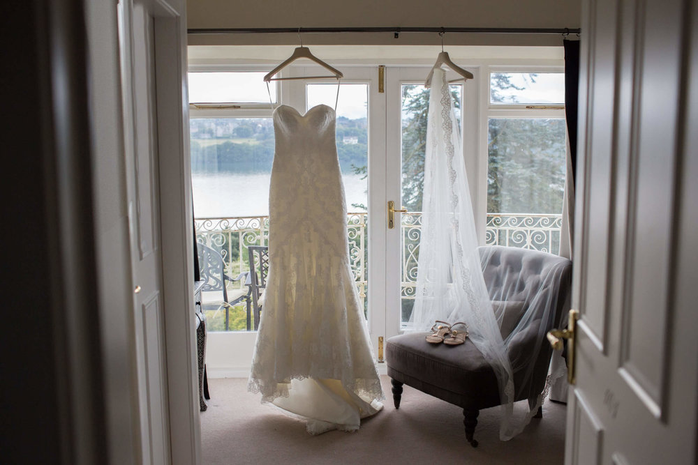 detail photograph of wedding dress hung hung on curtain rail with veil