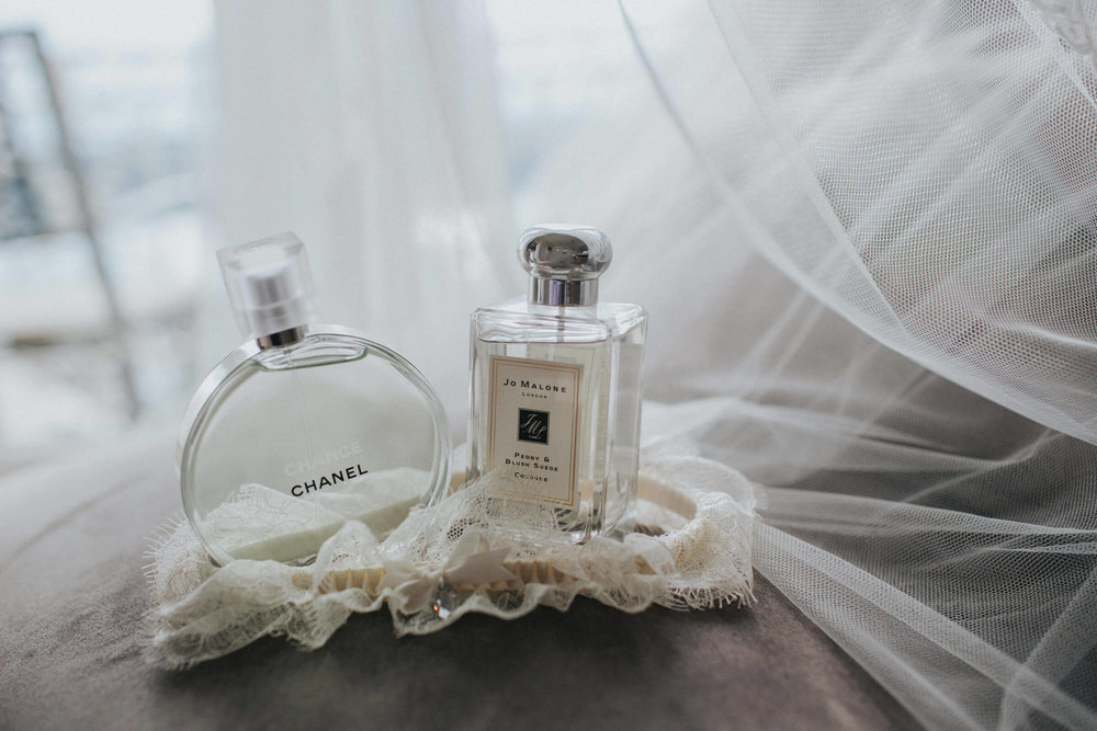 detail photograph of wedding perfume with bride garter and veil