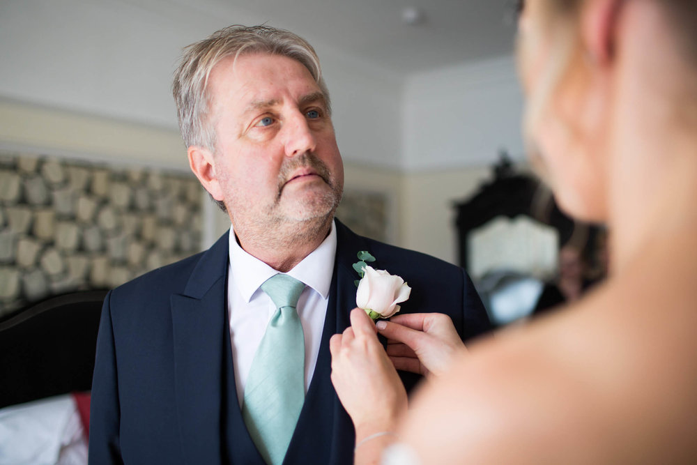 father of bride having pin-hole placed