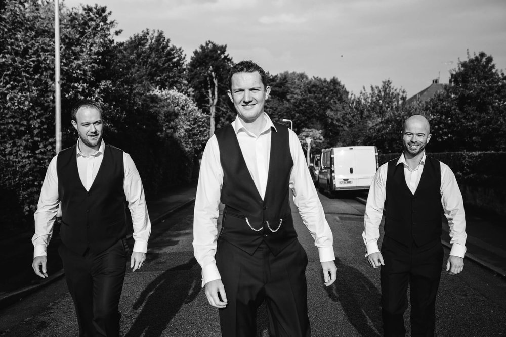 portrait of groom and groomsmen on road in Llandudno