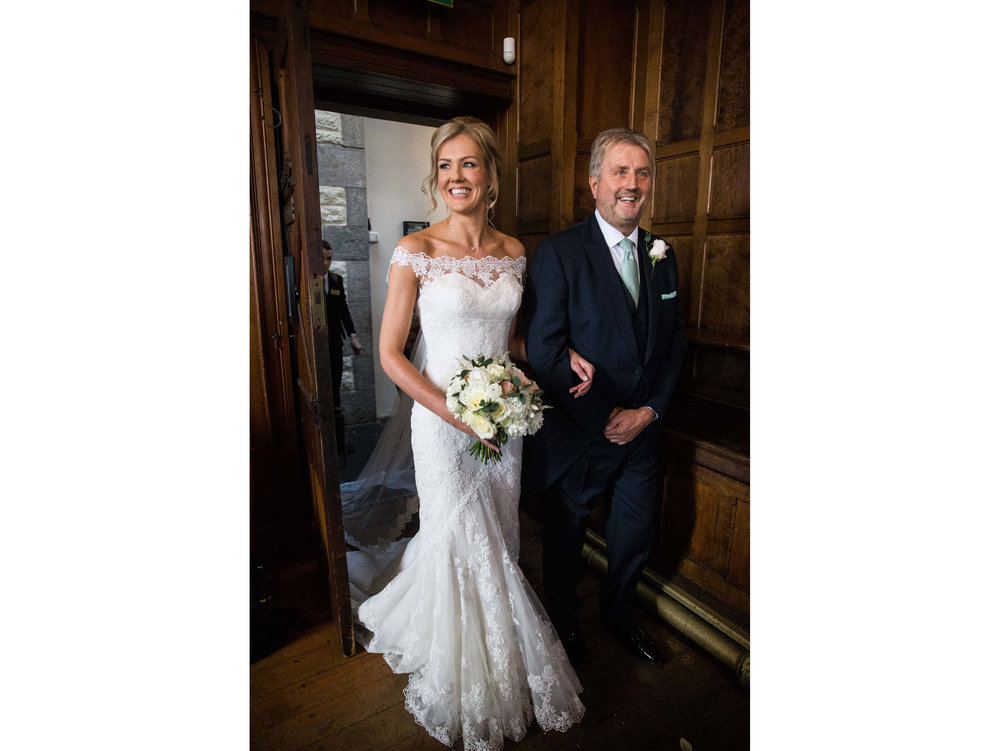 bride with big smile coming through the door with father arm in arm