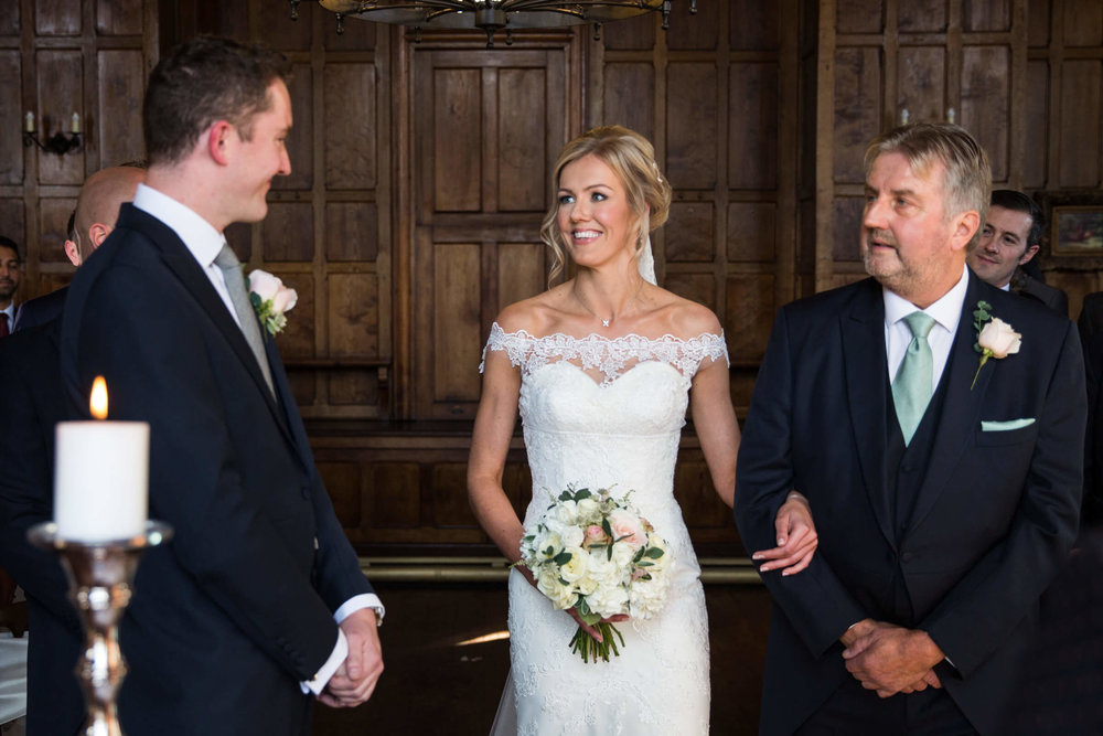 bride linked arms with father looking at groom on the aisle