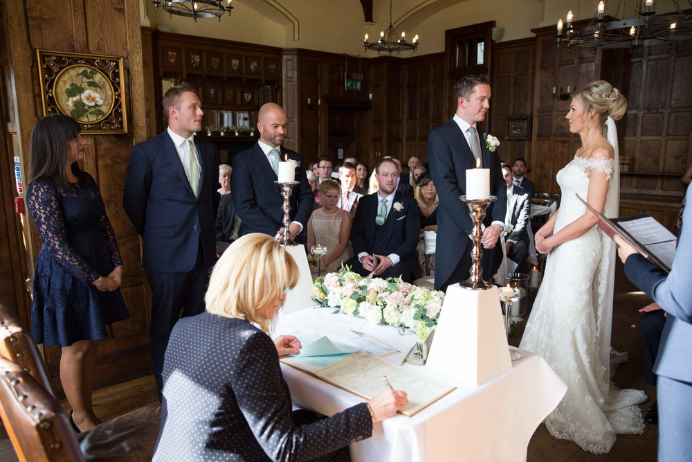 wide angle photograph of wedding vows in stunning banqueting hall