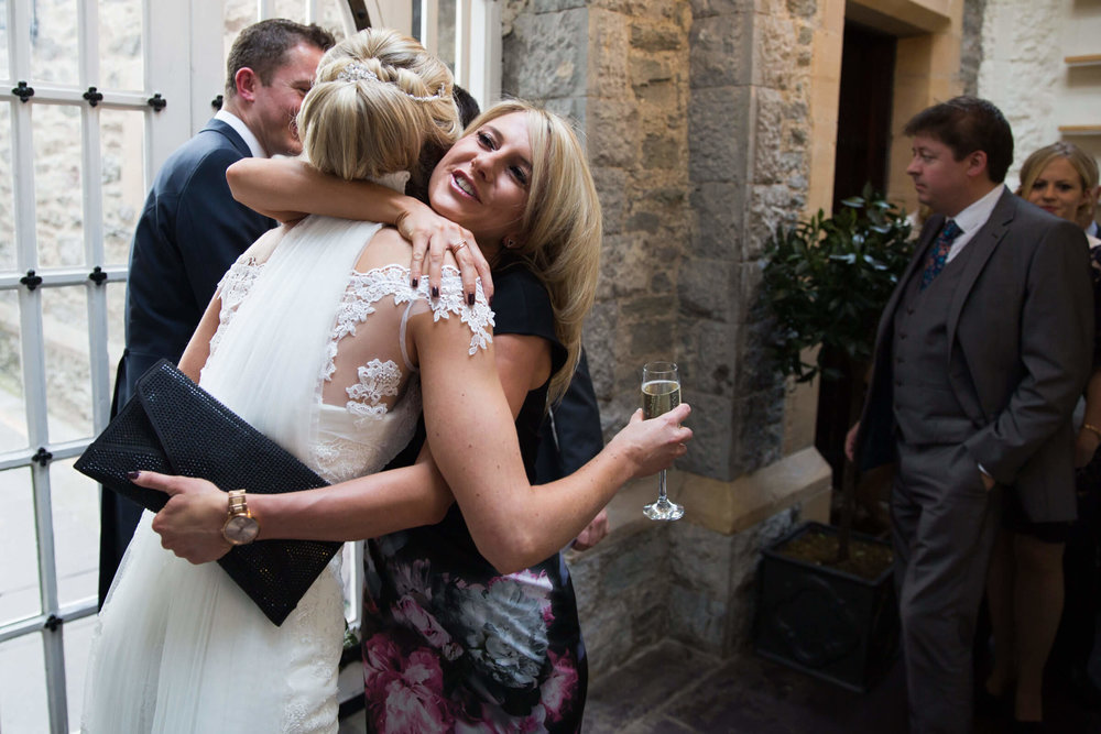 bride being hugged by guest after ceremony