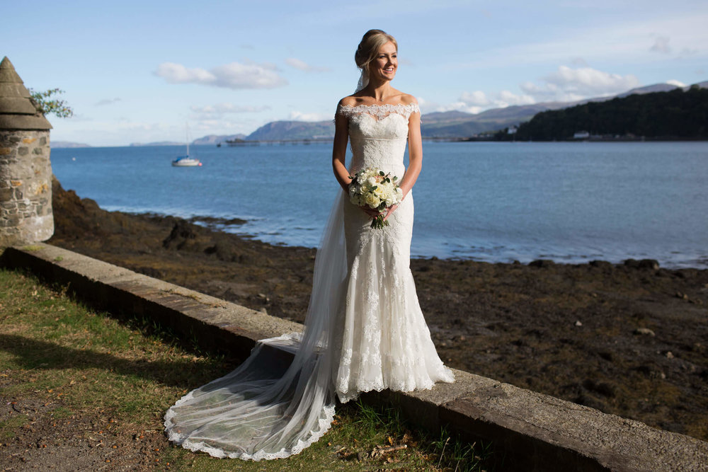 bride looking out on the Menai Strait with the Snowdonia Mountains as a backdrop