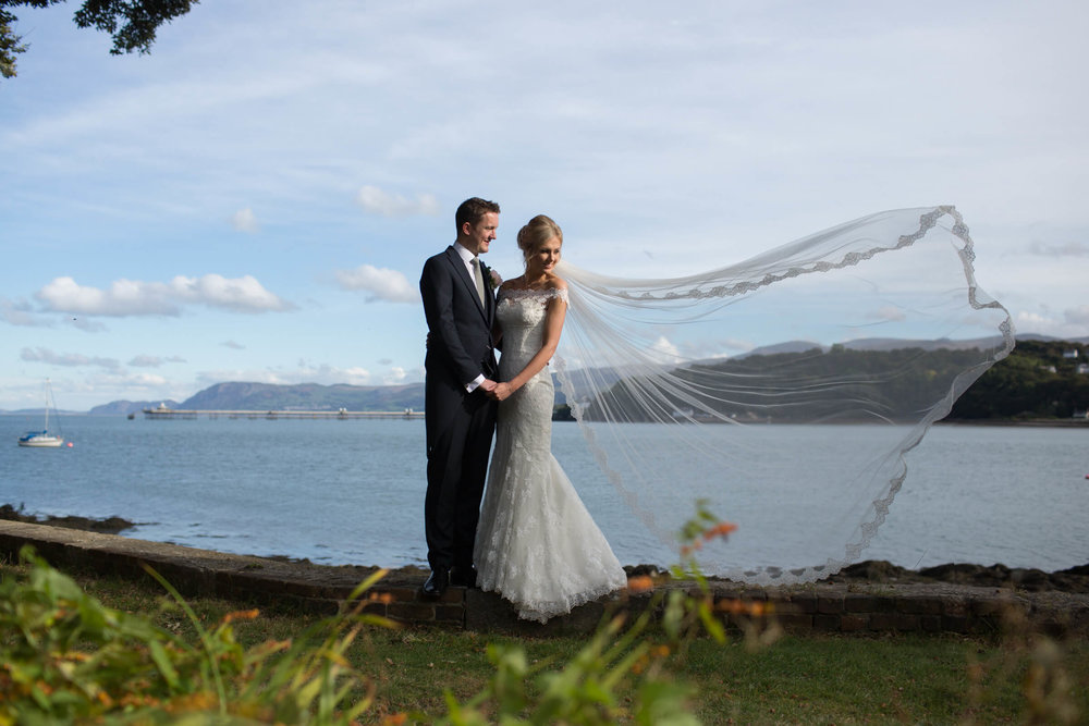 bride and groom looking out on the menai strait