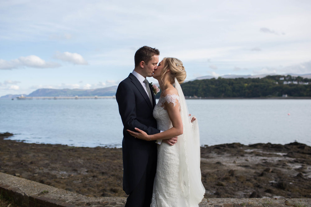 newlyweds kissing with the sea as a backdrop
