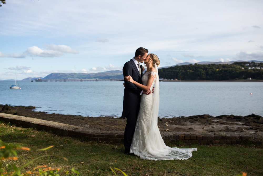 wider photograph of bride and groom kissing with menai strait background