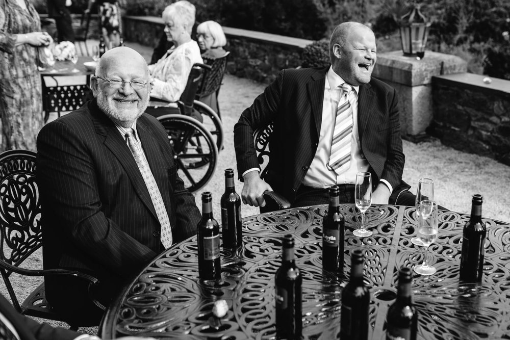 grooms uncles sharing a laugh in grounds of mansion