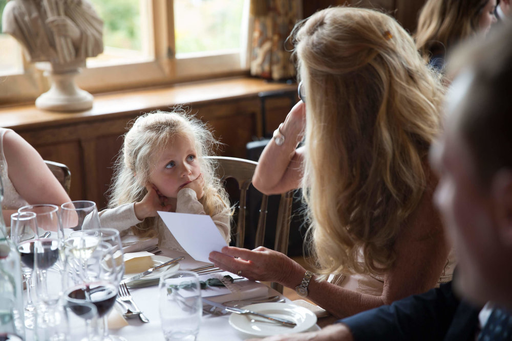 flower-girl sat at table looking at mum