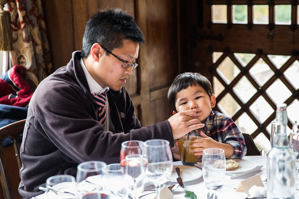 child being fed by dad sat at table
