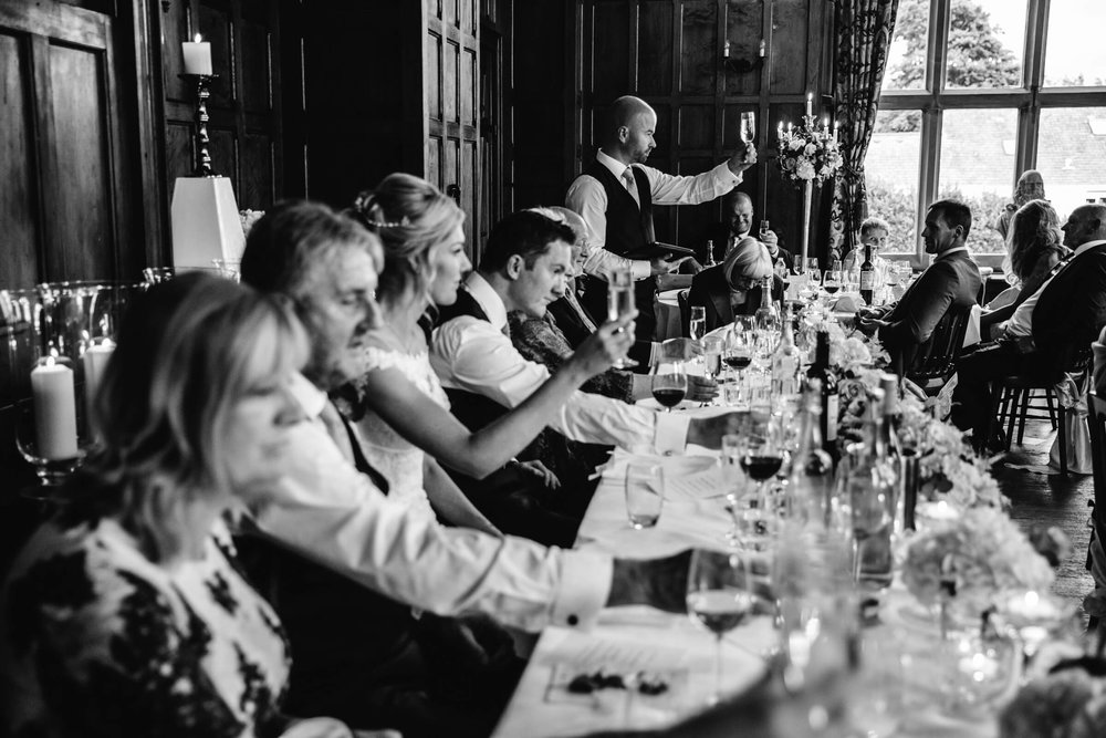 black and white photograph looking down the top table at best man raising a glass for speech