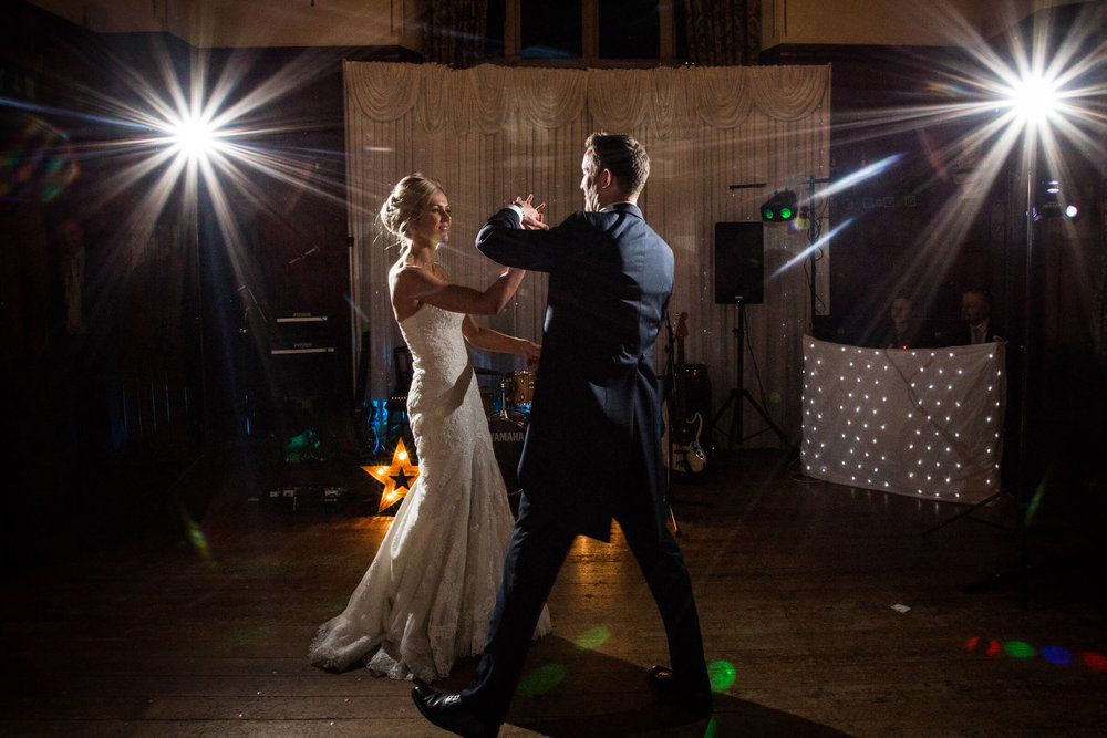 first dance pirouette of newlywed couple in banqueting suite