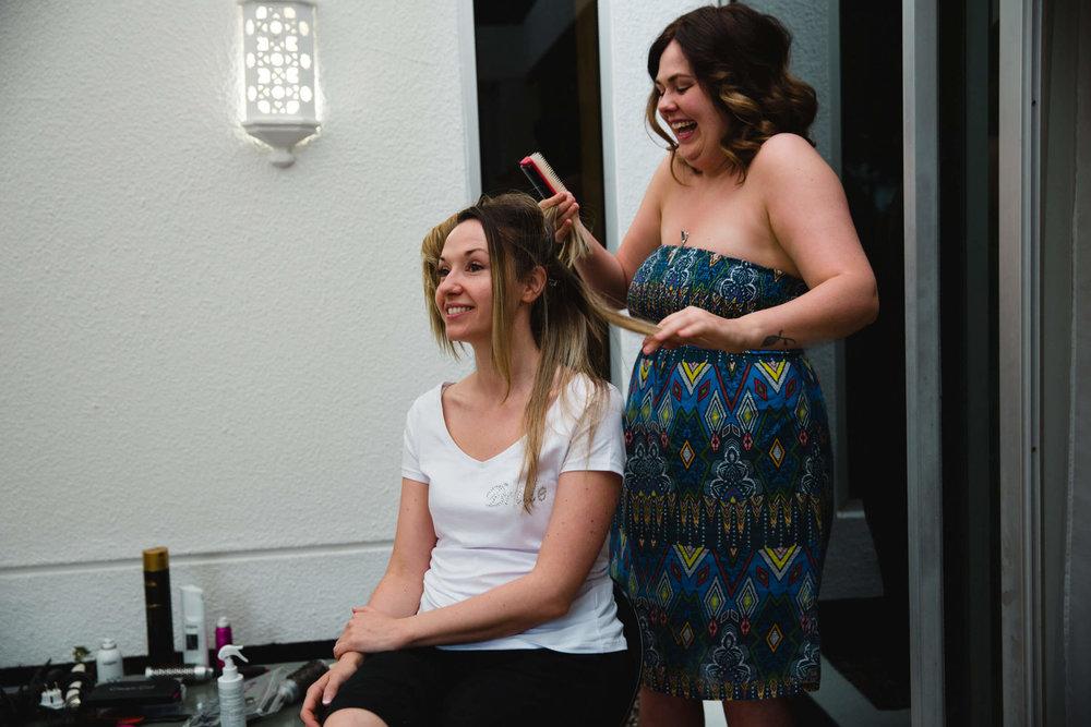 bride having hair styled on terrace