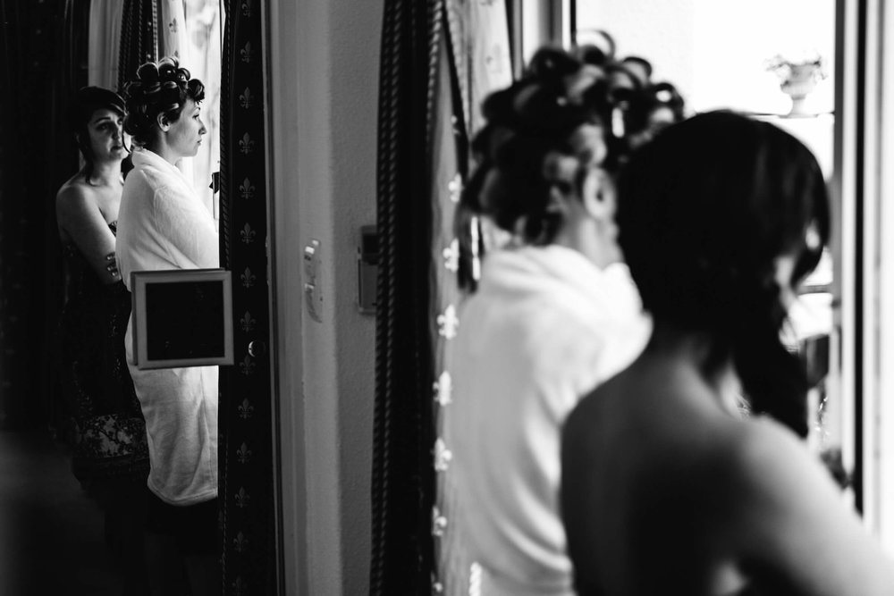 black and white photograph of bride and friend looking out of window at swimming pool