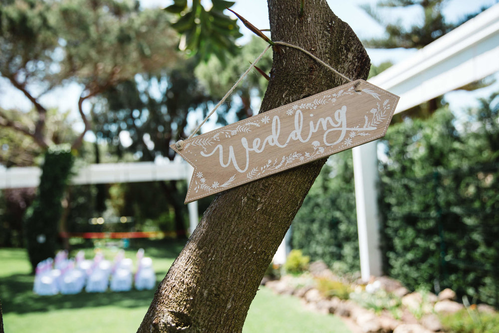 wedding sign hung on tree in garden of vilamarques