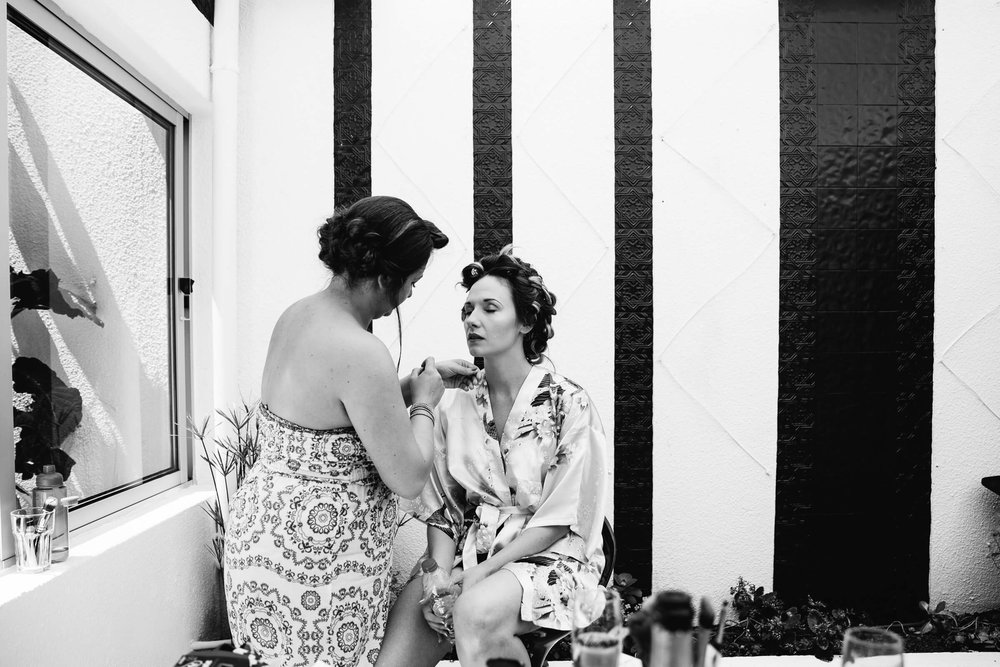 black and white photograph of bride having make up