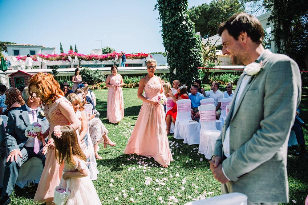 Bridesmaid smiling at Groom in aisle at vilamoura wedding