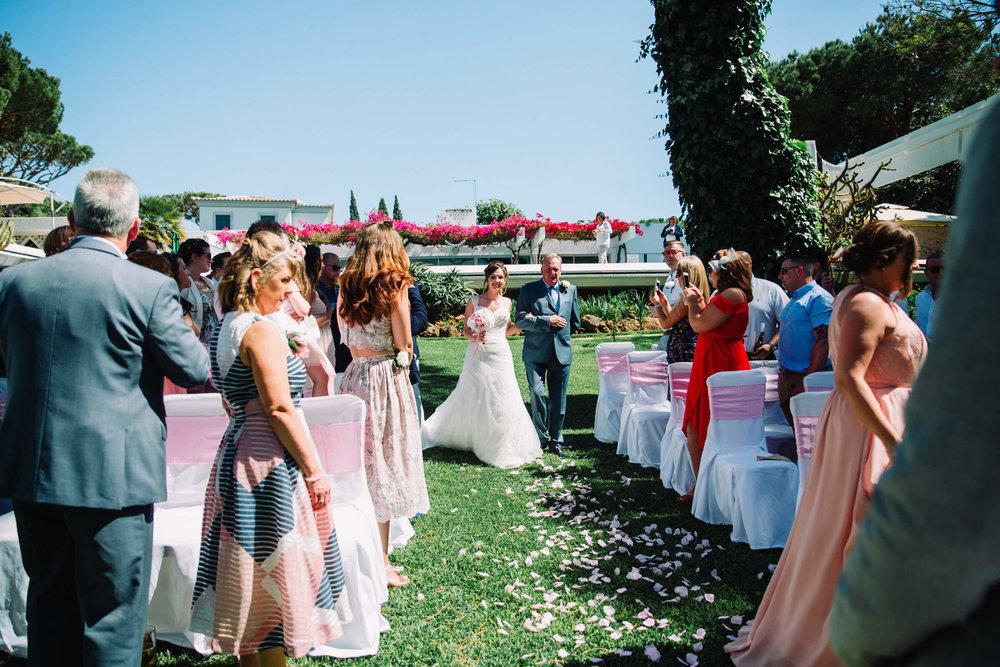 bride walking down aisle in outdoor garden ceremony at vilamaques in portugal