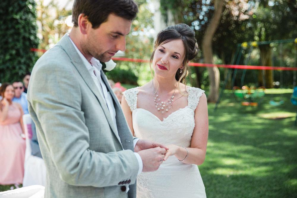bride looking at groom and exchanging wedding rings