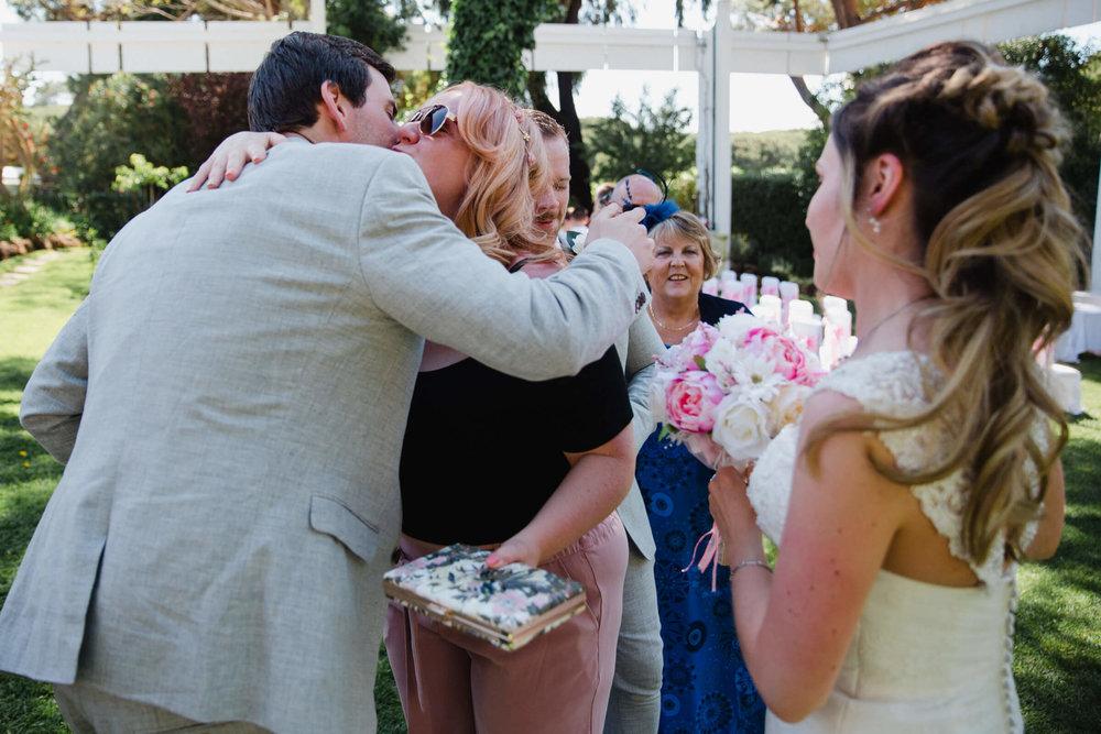 groom hugs friend after wedding