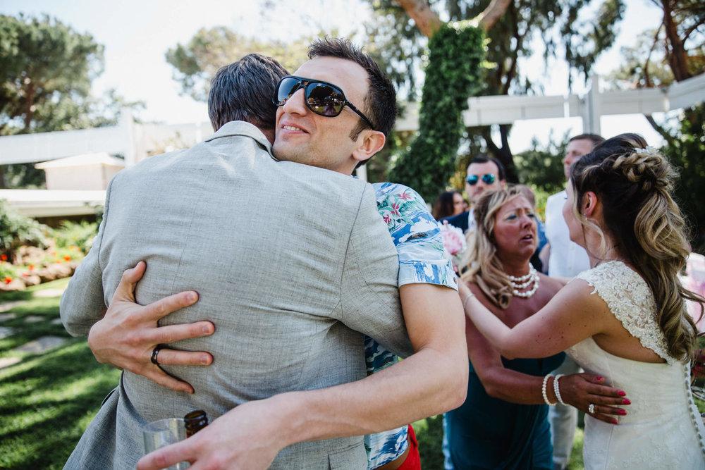 groom hugs friend after wedding ceremony