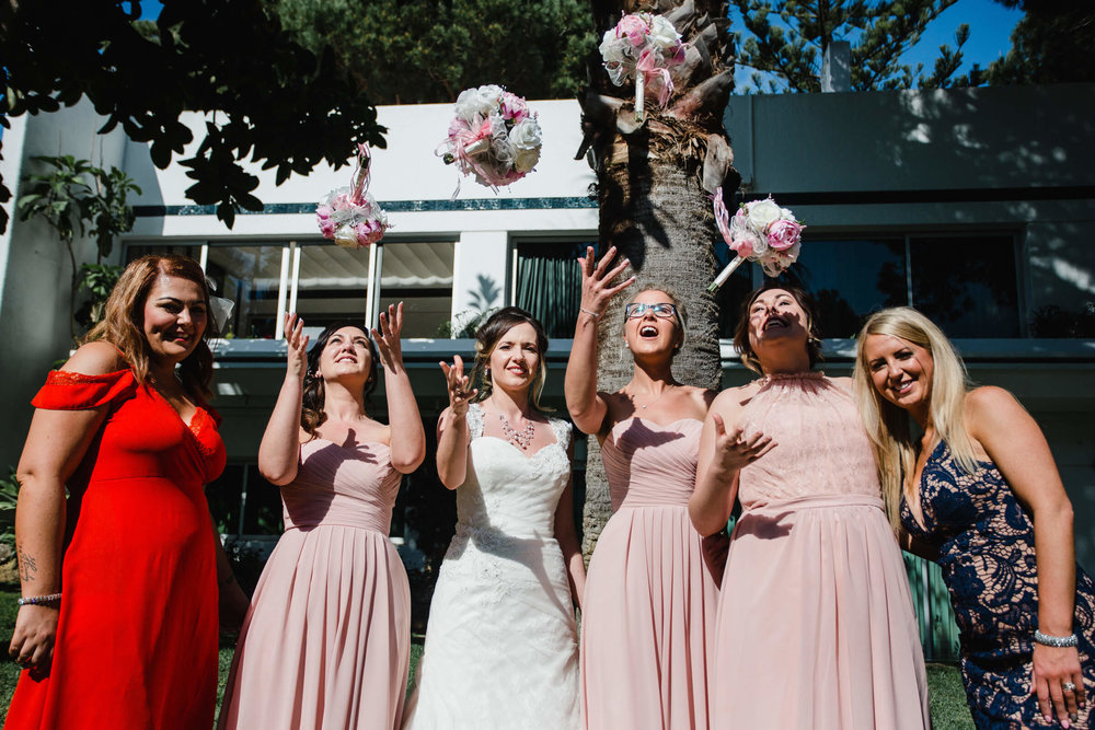 bride and bridesmaides throwing bouquets in air