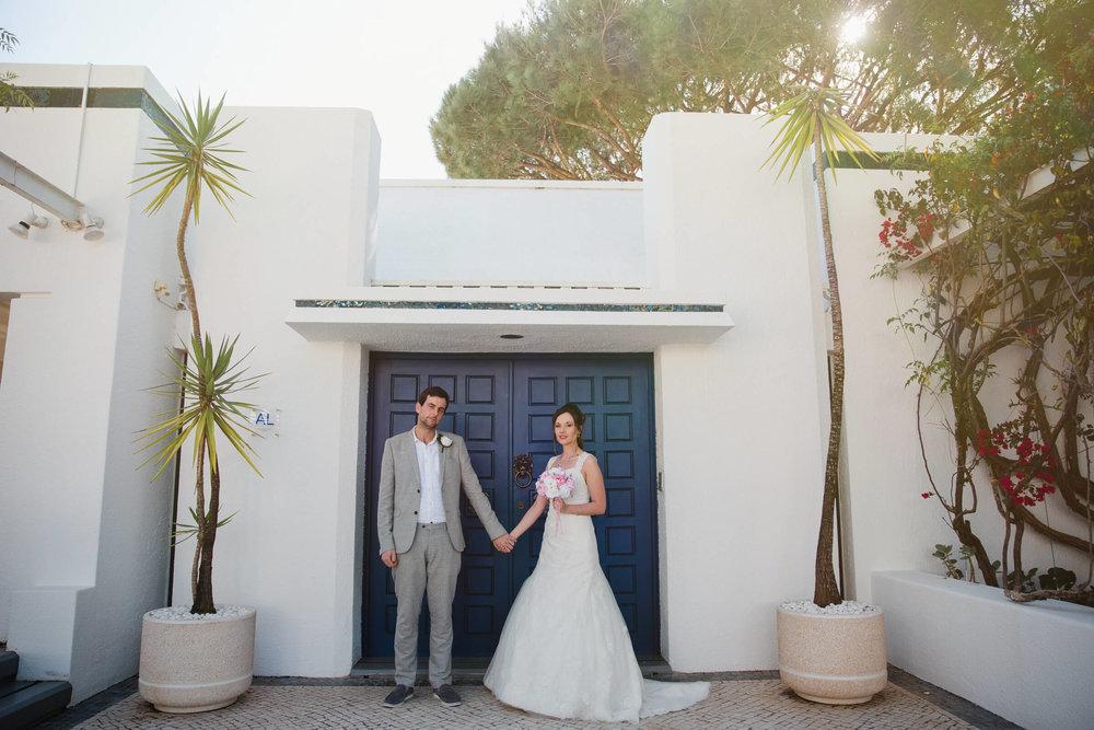 bride and groom in blue doorway of villa