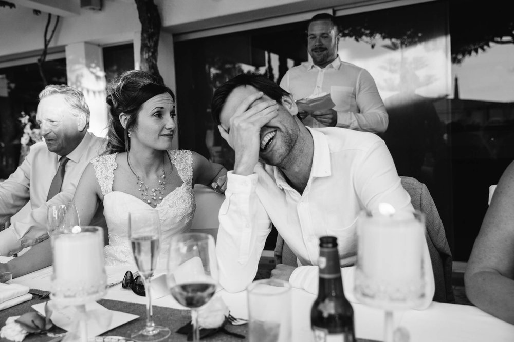 groom with head in hands laughing at best man speech