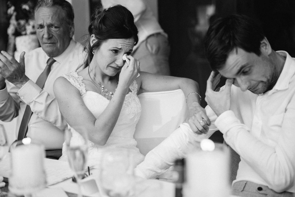 black and white photograph of the bride and groom both crying after the best man speech