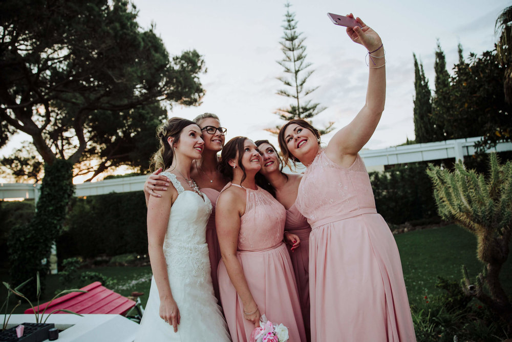 bridal party talking a photograph using a phone camera