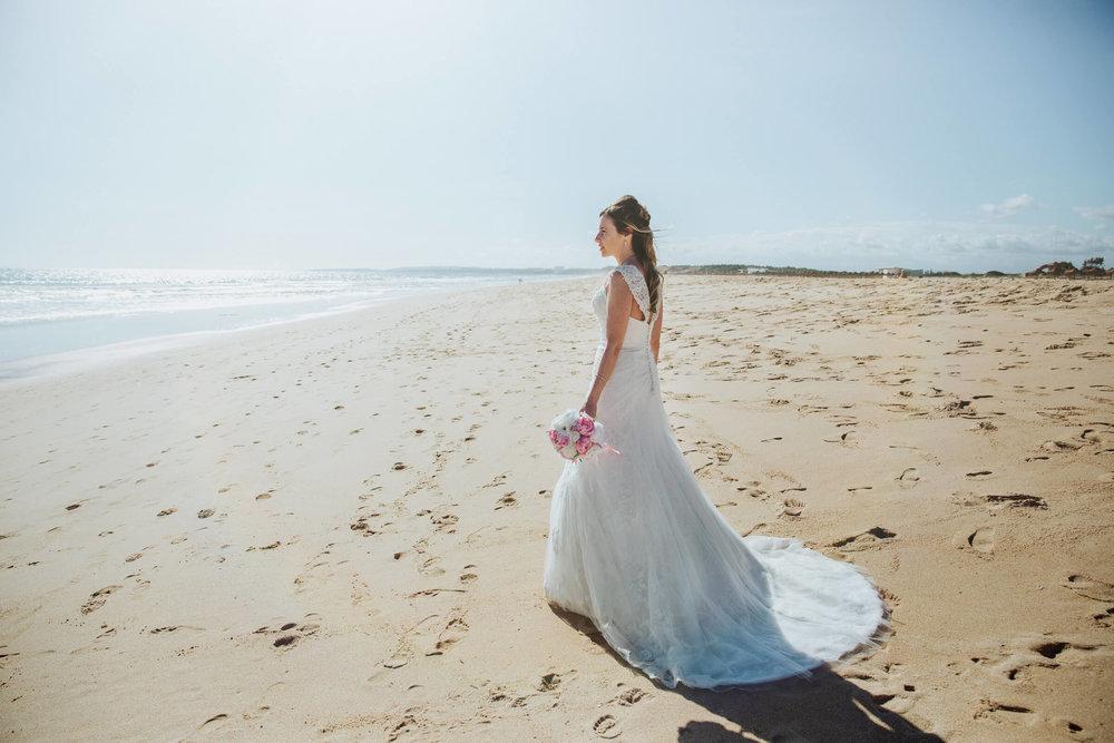bride holding bouquet on beach at tivoli hotel vilamoura marina
