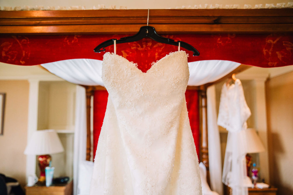 close up detail photograph of wedding dress hung on four poster bed