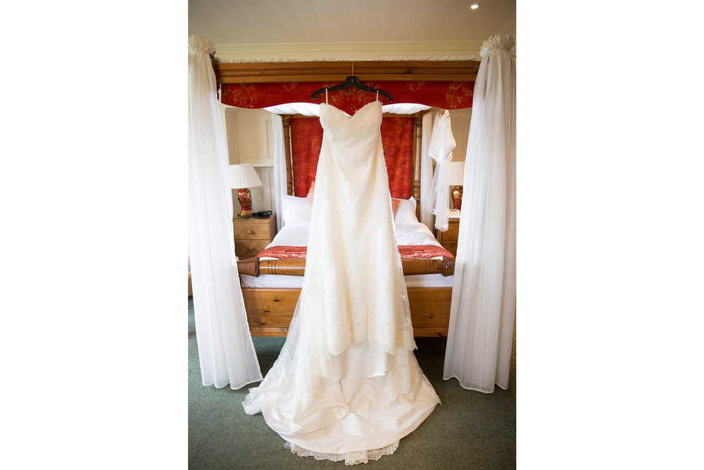wedding dress hung from the four poster bed
