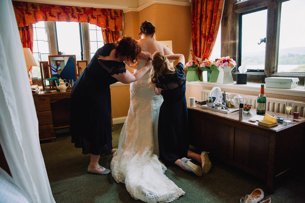 bridesmaids helping bride with wedding dress in front of mirror