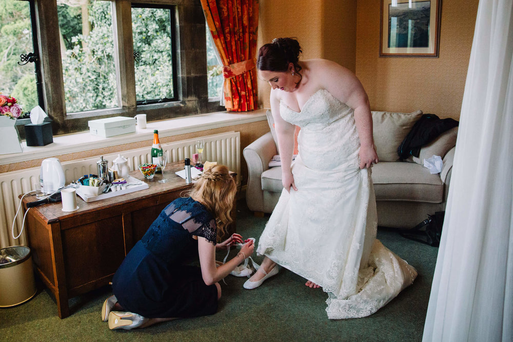 maid of honour helping bride put on shoe
