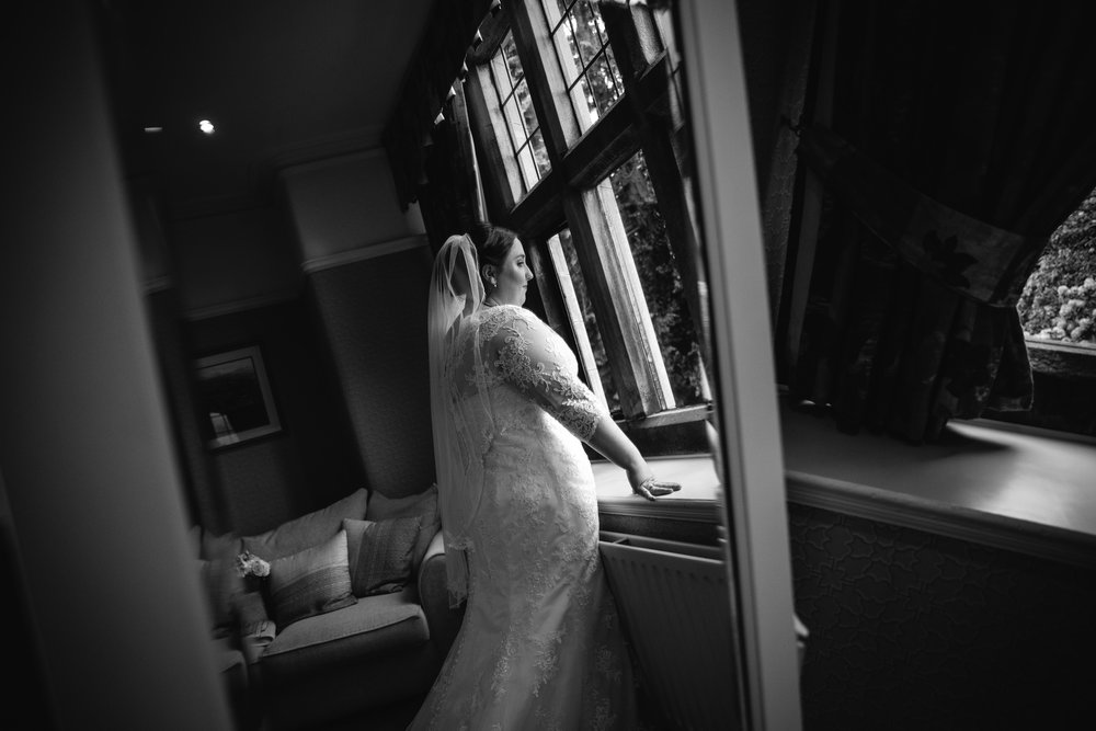 bride reflection portrait in the mirror looking out of window in bridal suite