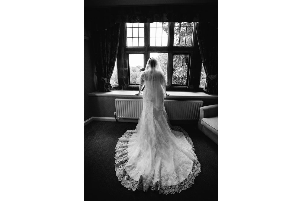 black and white photograph taken behind bride looking outside of window