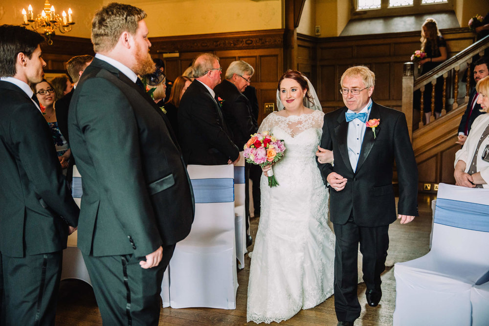 Bride walking down the aisle with her father looking at Groom