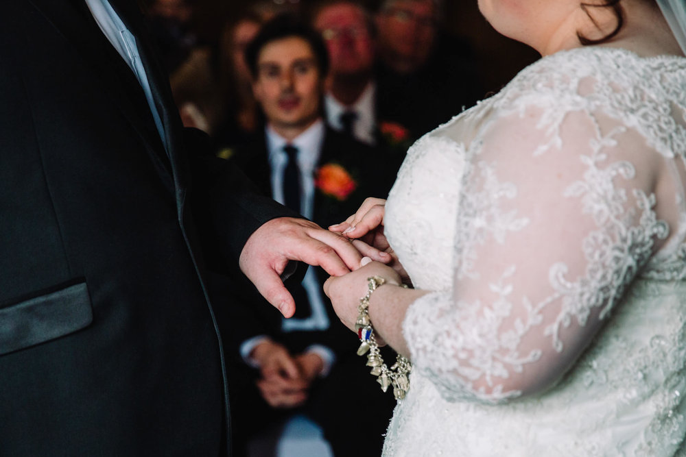 close up photograph of the exchanging of wedding rings