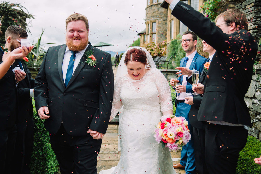 guests throwing confetti on to bride and groom