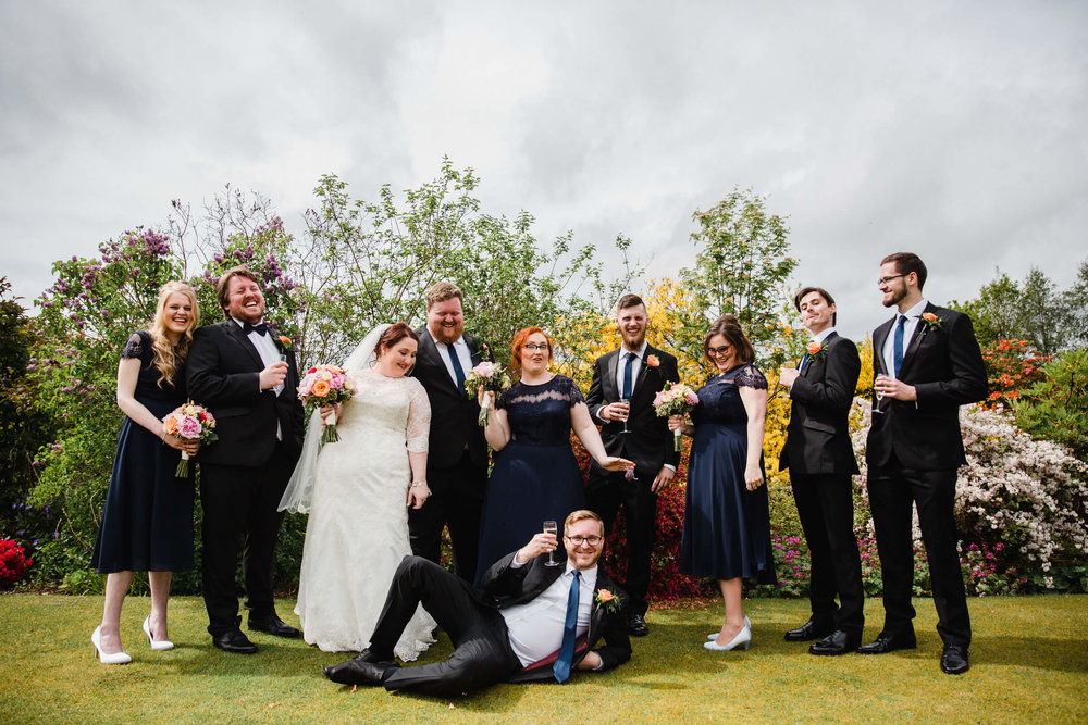 group shot of bride and groom and wedding guest friends in gardens of house
