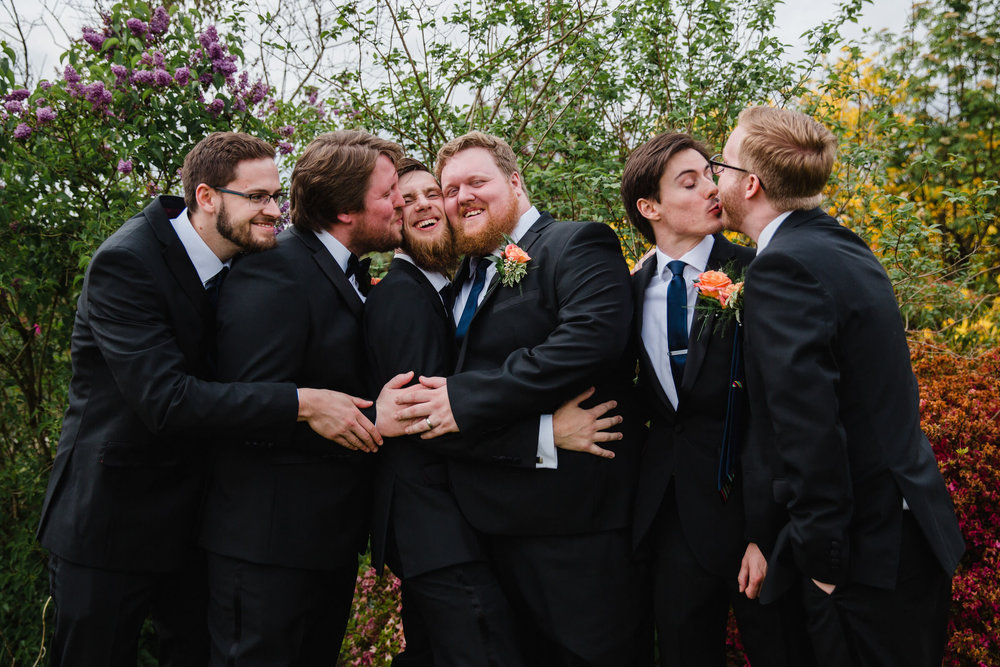 groomsmen kissing in gardens for a group photograph