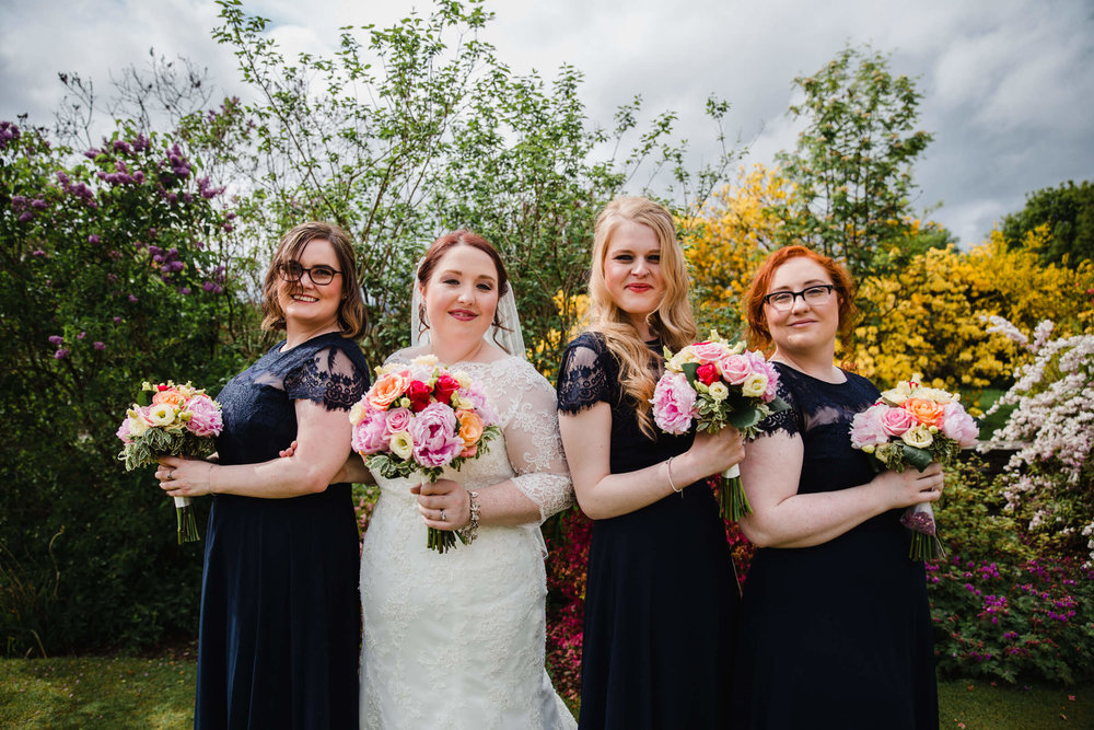 bride with bridesmaids all holding bouquets for a portrait in gardens