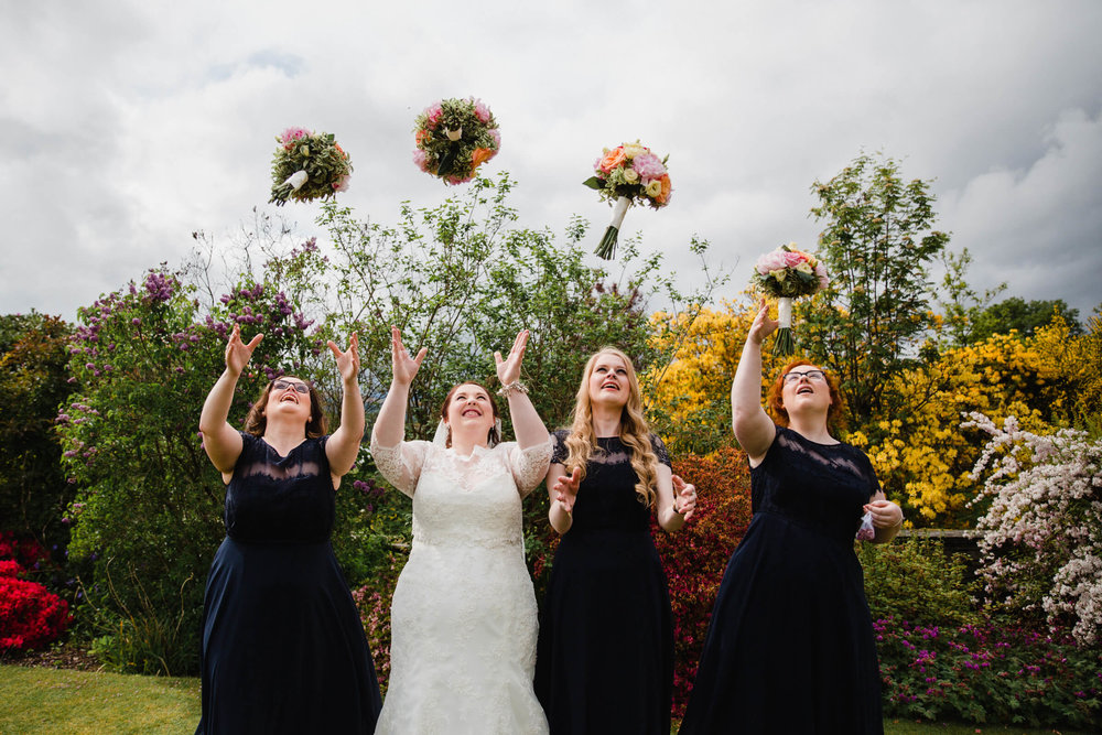 bride and bridesmaids throwing bouquets in air together